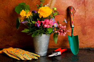 A colourful garden trowel, gloves, and clippers resting next to a tin pot of cut flowers.